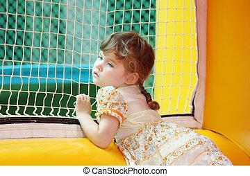 Little beautiful girl in dress stands in yellow bouncy castle