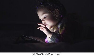 Little beautiful girl looking Tablet lying on the bed in the...