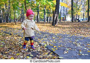 Little beautiful girl walking alone in autumn park