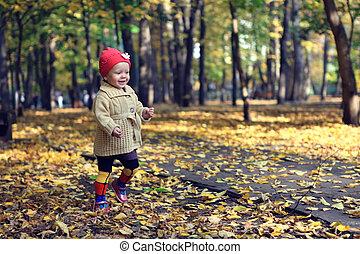Little beautiful girl walking in autumn park