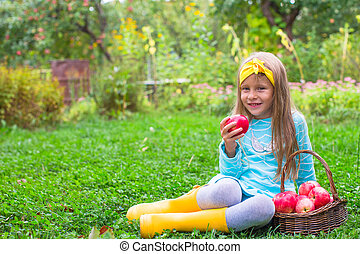 Little beautiful girl with a basket of apples in autumn time