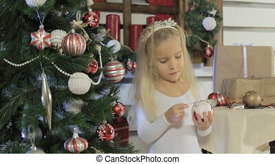 Little beautiful girl with long blond hair decorates the Christmas tree