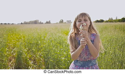 Little beautiful light and blond girl with chamomile flowers in hands posing and spinning on a summer day.
