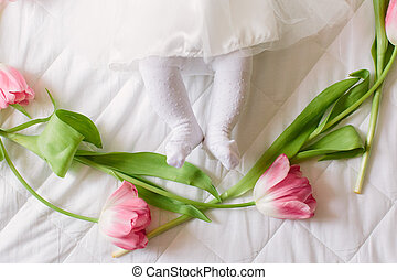 Little beautiful newborn girl lying on the bed among the flowers