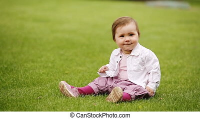 Little beautiful pretty baby-girl sitting on the green grass in the city-park.