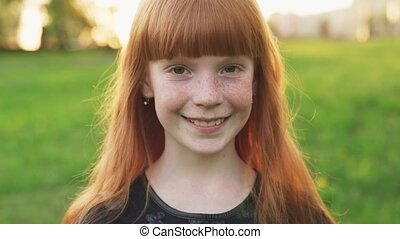 Little beautiful redhead girl with freckles smiling and looking at camera