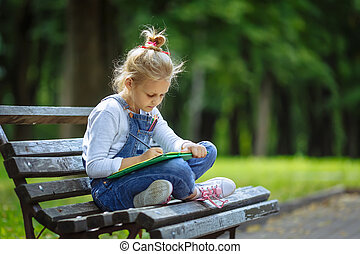 Little beautiful school girl drawing with colored pencils, sitting on a bench in sunny park
