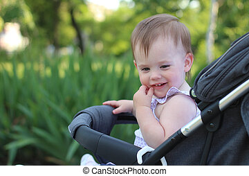 little, beautiful, smiling, cute redhead baby in a pram out-of-doors in a sleeveless shirt looking down