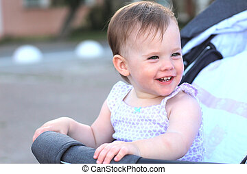 little, beautiful, smiling, cute redhead baby in a pram out-of-doors in a sleeveless shirt