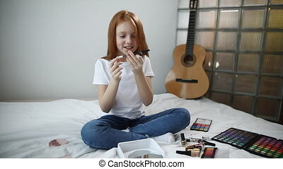 little blogger talks about cosmetics, records a video sitting in front of the camera. cosmetics the concept of beauty.