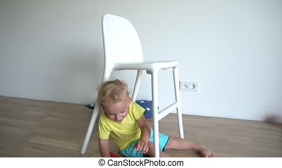 Little blond baby boy playing with teddy bear sitting under chair. Gimbal motion