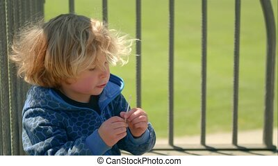 Little blond boy eating a candy savory