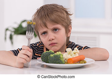 little blond boy eating at kitchen. unhappy child sitting at...