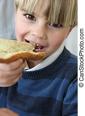 little blond boy eating slice of bread and butter