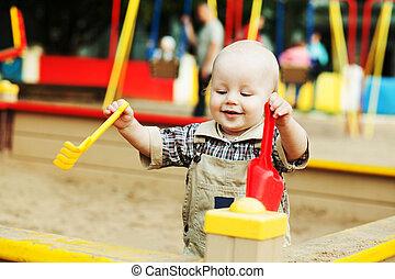 little blond boy enjoys playing in the sandbox