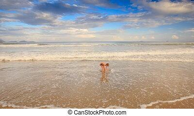 Little Blond Boy Gambols in Foamy Waves of Shallow Sea on Beach