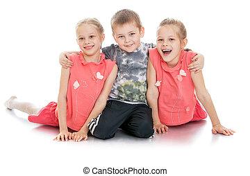 Little blond boy hugging his favorite sisters
