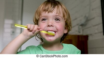 Little blond boy learning brushing his teeth in domestic...