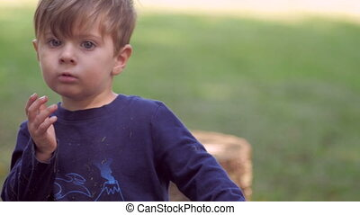 Little blond boy looking at camera waving and playing with toy in slow motion