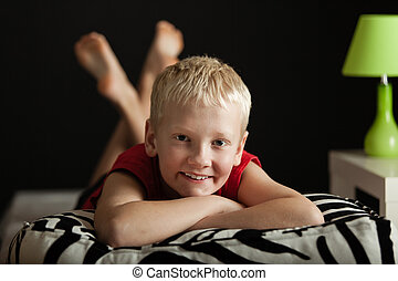 Little blond boy on zebra patterned pillow