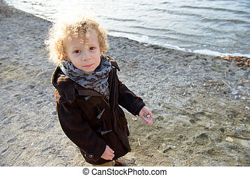 Little blond boy playing on the beach one day autumn