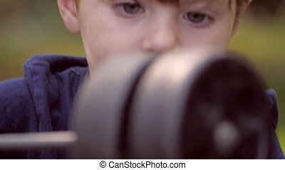 Little blond boy playing with wheels from toy car close up -...