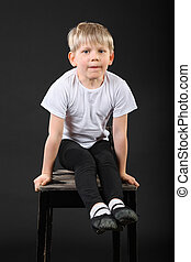 Little blond boy pull on his hands at old stool in black studio
