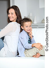 Little blond boy sitting on sofa with mom