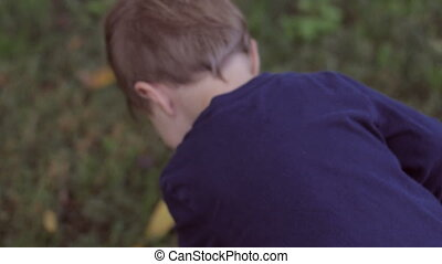 Little blond boy walking on grass while camera follows him...