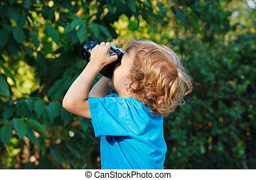 Little blond boy with a camera outdoors
