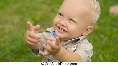 Little blond boy with blue eyes looking up the sky raising hands, sitting on green grass
