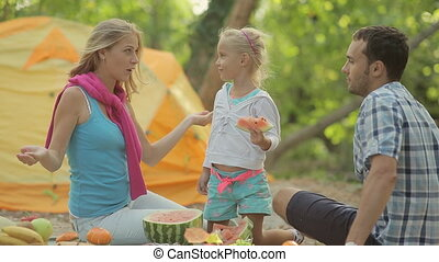 Little blond girl eating a slice of watermelon at the picnic in the forest