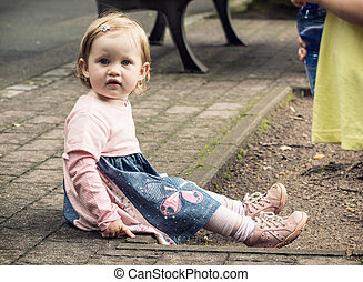 Little blond girl in beautiful dress sitting on the ground...