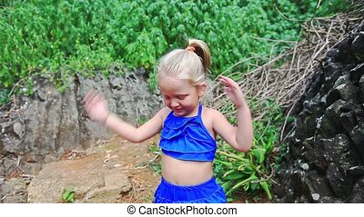 Little Blond Girl in Blue Gambols on Path against Green Plants