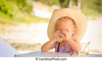 Little Blond Girl in Hat Drinks Juice from Glass