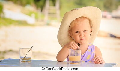 Little Blond Girl in Large Hat Drinks Juice with Spoon