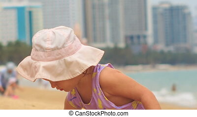 Little Blond Girl in Panama Plays with Toy on Beach