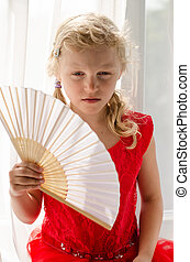 little blond girl in red dress with fan