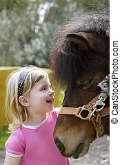 little blond girl loves her pony funny portrait