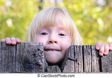 Little Blond Girl Peeking Over a Wooden Fence
