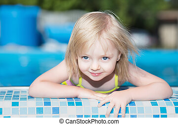 Little blond girl posing in water pool