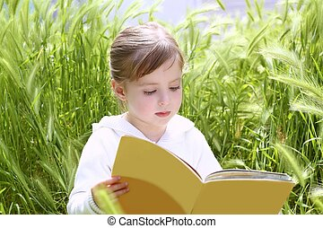 little blond girl reading book green spikes garden