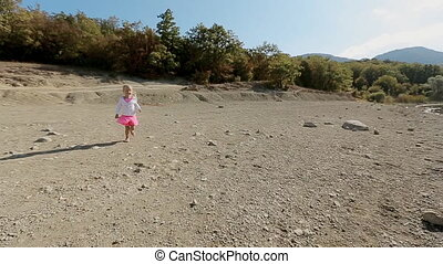 Little blond girl running toward father and he whirls her in slow motion