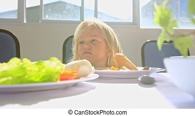 Little Blond Girl Sits at White Table Laughs Gambols