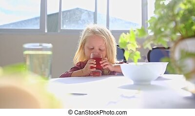 Little Blond Girl Sits at White Table Drinks Juice