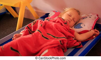 Little Blond Girl Sleeps on Bed under Red Blanket