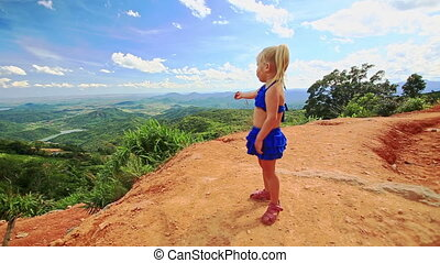 Little Blond Girl Stands on Sand Dune Crest over Valley -...