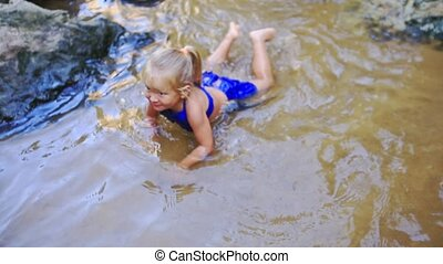 Little Blond Girl Swims on Shallow Pond Sandy Bottom