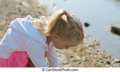Little blond girl throwing stones into the water of the pond...