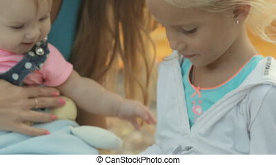 Little blond girl with her family on the nature plays on the tablet
